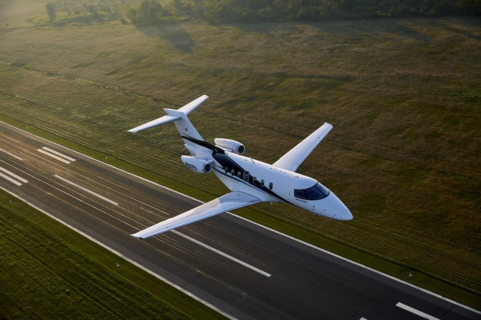 Pilatus PC-24 light jet flies above a runway