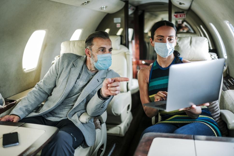 Executives work on a Cessna Citation business jets wearing face masks