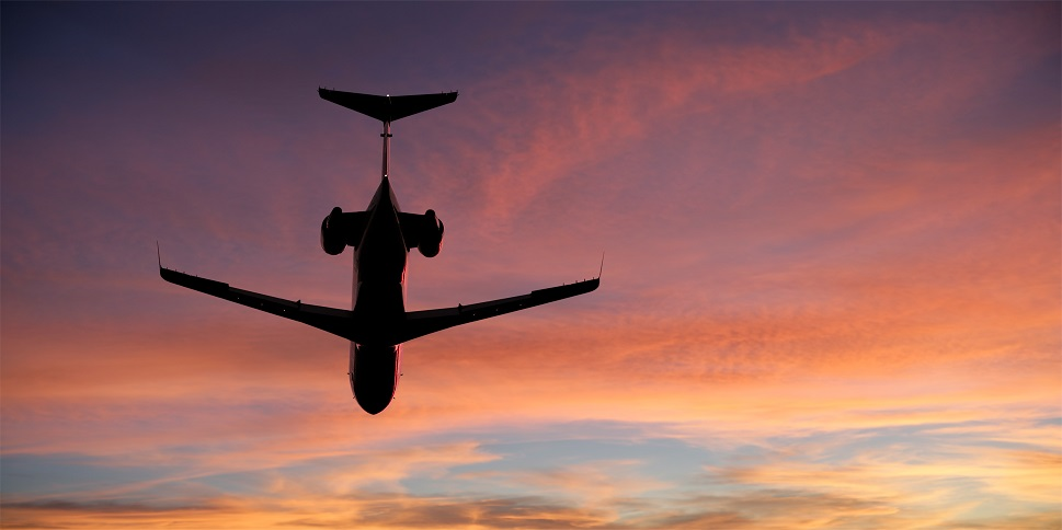 Private jet flies overhead at sunset
