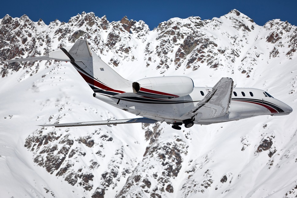 A Cessna Citation mid-size jet landing at mountain airport