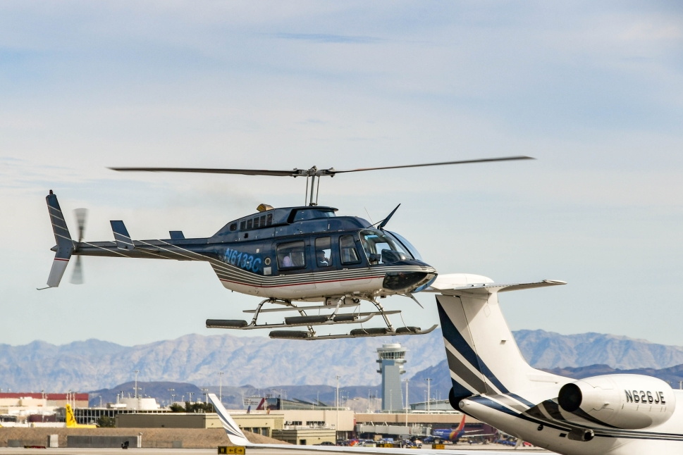 A helicopter landing close to a Gulfstream private jet