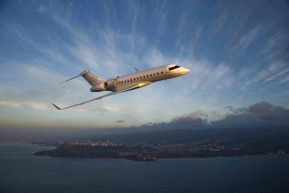 Bombardier Global 6000 private jet flying over ocean
