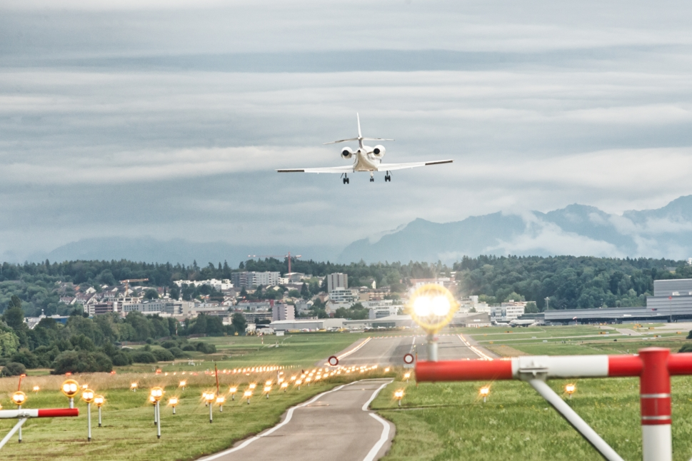 Business jet flies in to land on airport runway