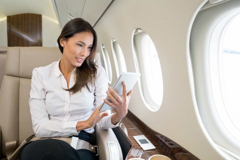 Business jet passenger looks at her iPad