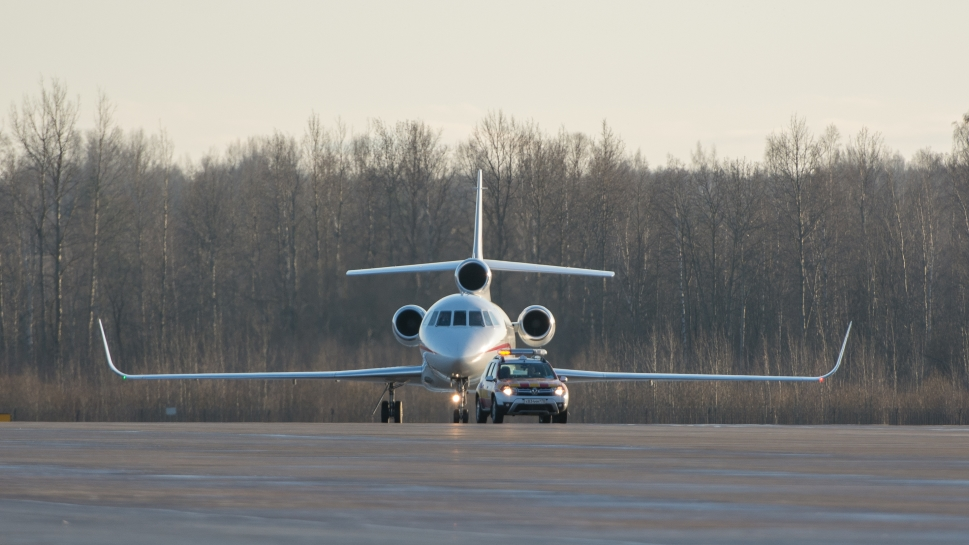 Dassault Falcon Jet Being Escorted to Airport Ramp
