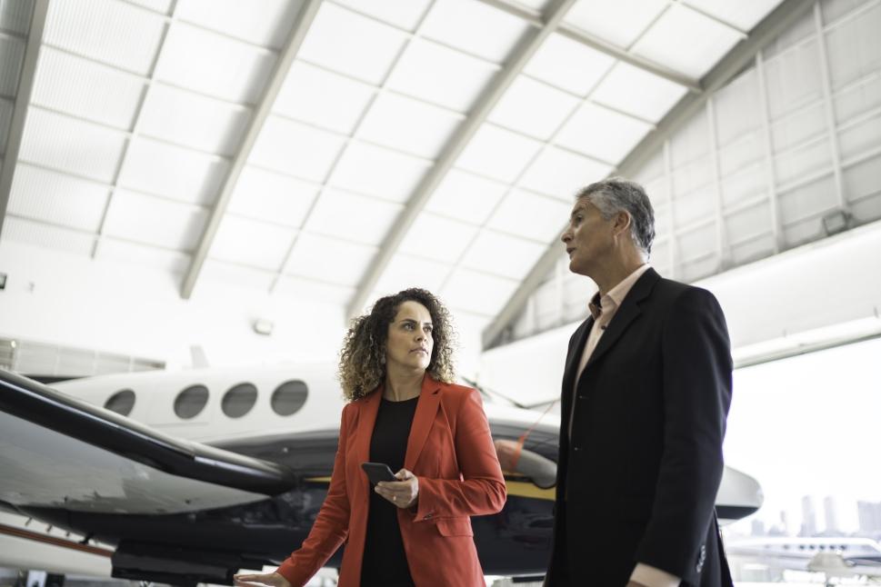 Executives Walk in Front of Beech King Air Turoprop in Hangar