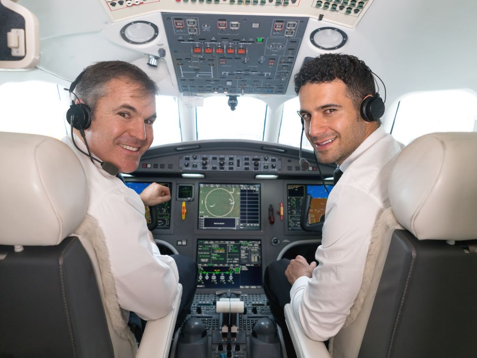 Happy pilots in a private jet cockpit