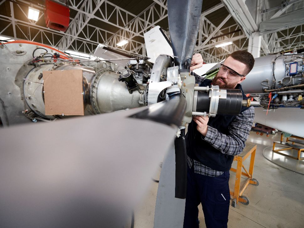Aircraft Mechanic works on a turboprop engine