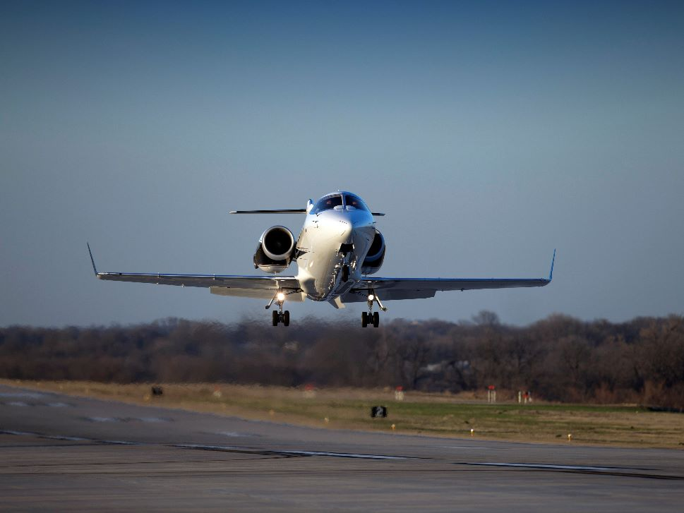 An older light jet lands at a private airport