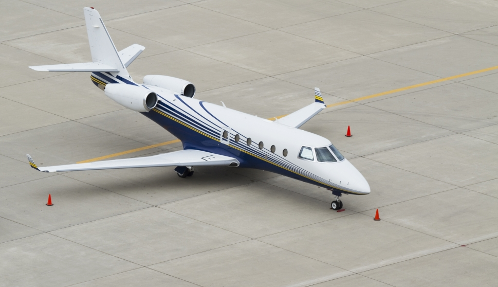 Older private jet parked on airport ramp
