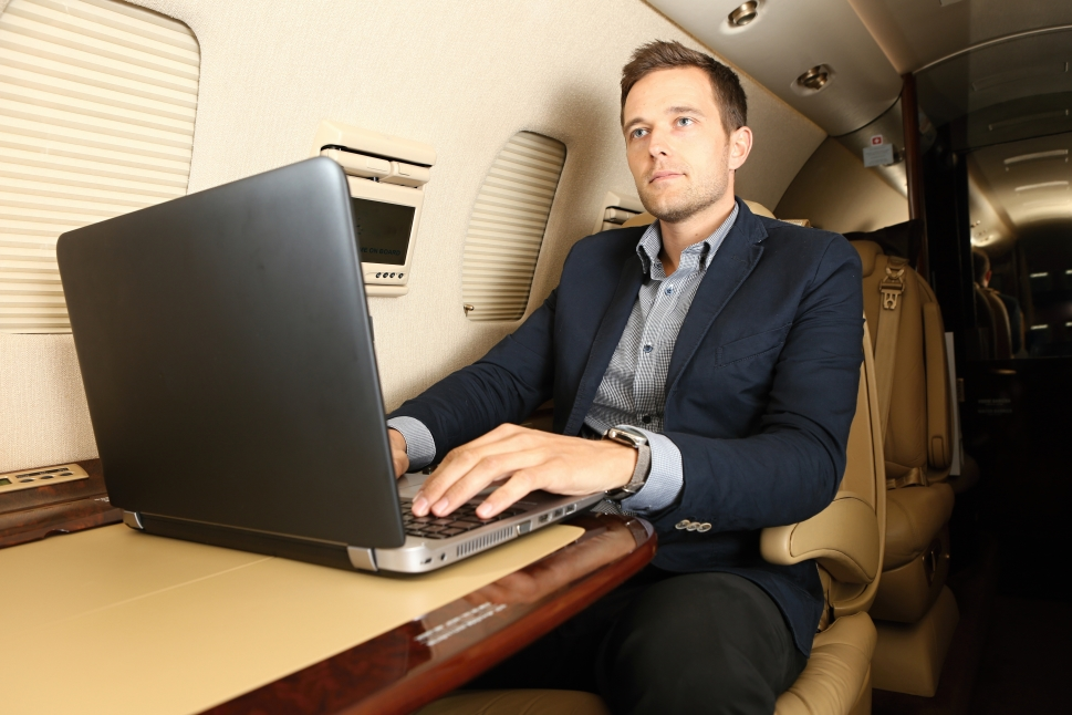 Private jet passenger works on his laptop in flight