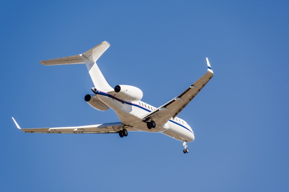 Private Jet Flies Overhead in Clear Blue Sky