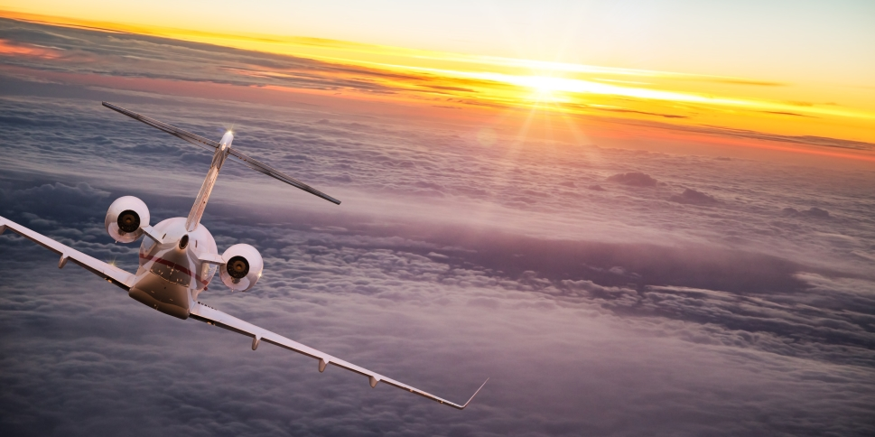 Private jet flies towards the sun