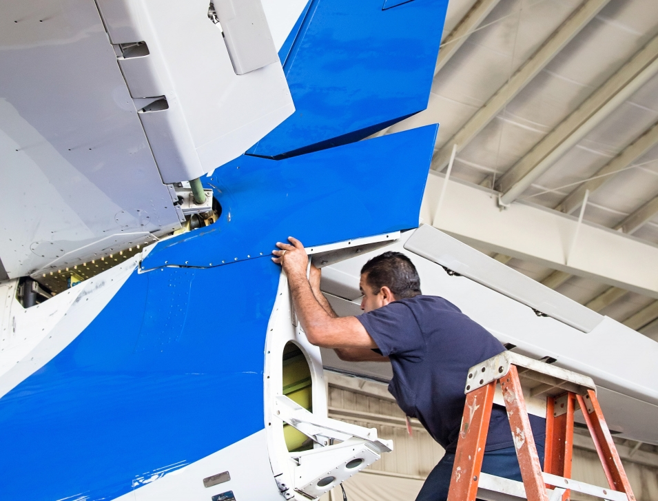 Private Jet Mechanic Works on Rear End of an Aircraft