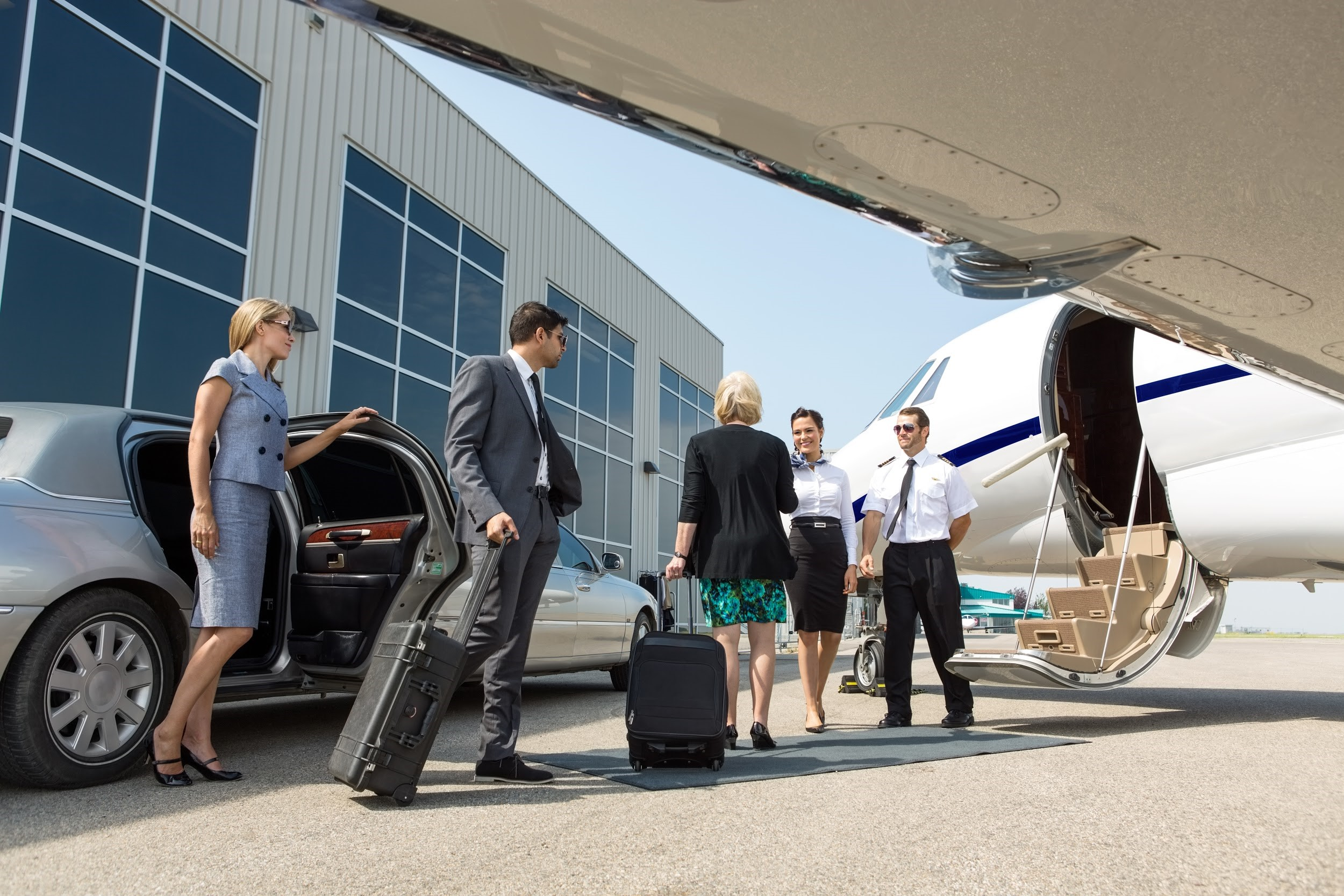 Passengers are greeted by two flight attendants while boarding a white private jet on a runway