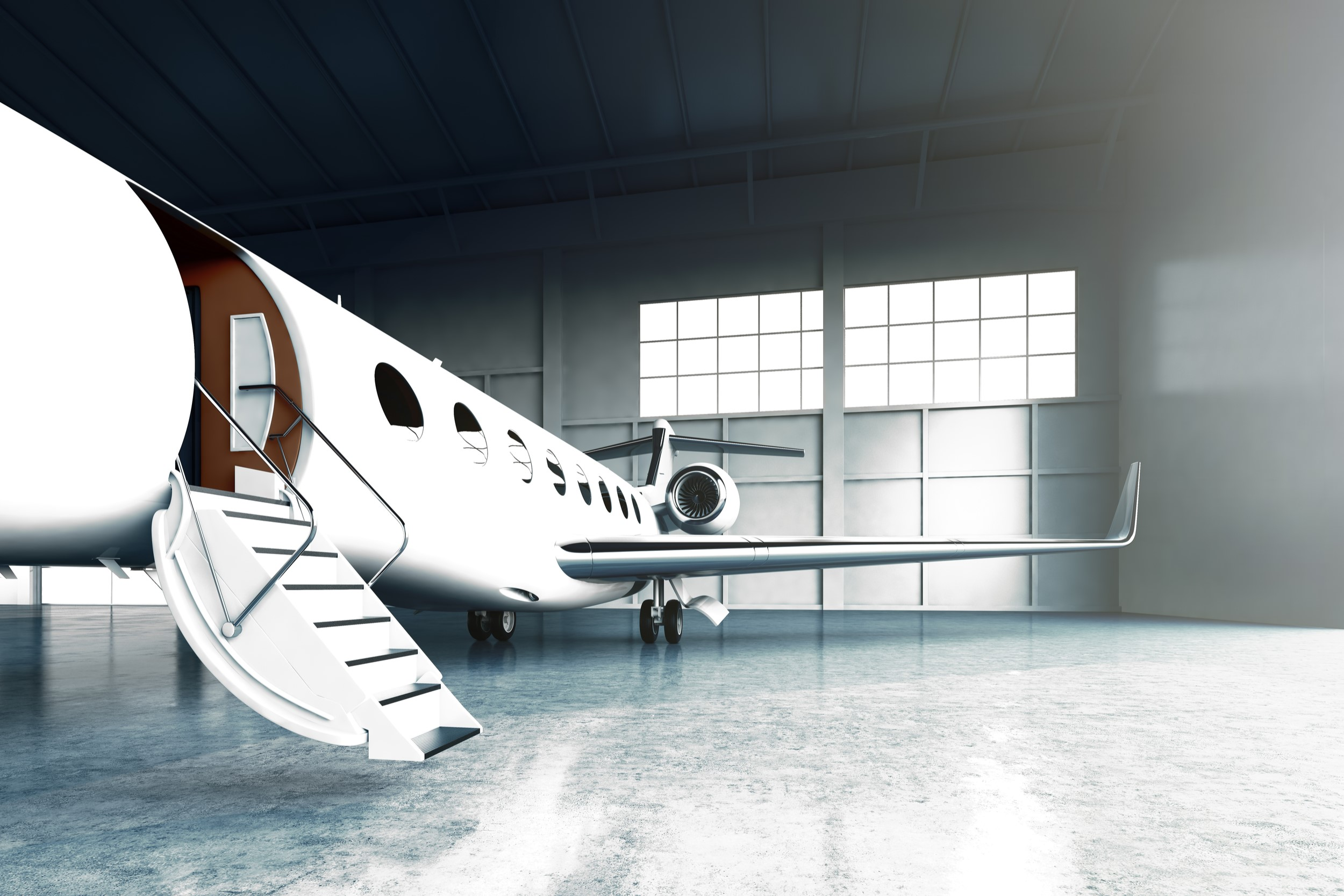 A white luxury private jet sits in a hangar with its door open