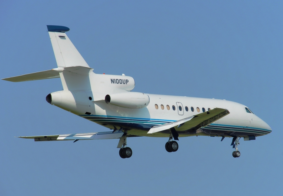 Dassault Falcon 900B private jet soars through a clear blue sky