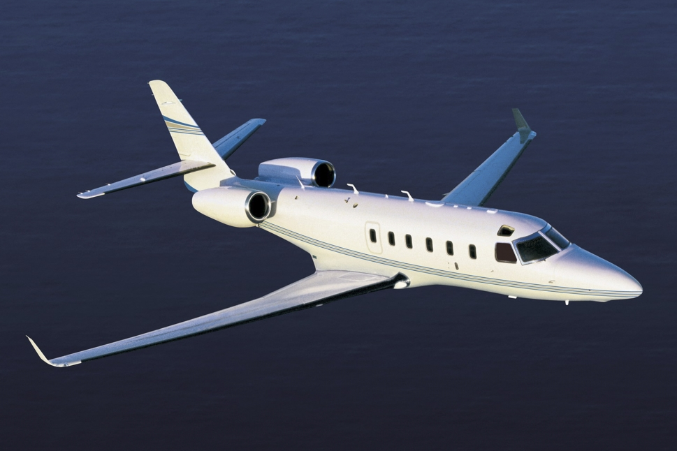 A Gulfstream G100 mid-size private jet flying across the ocean