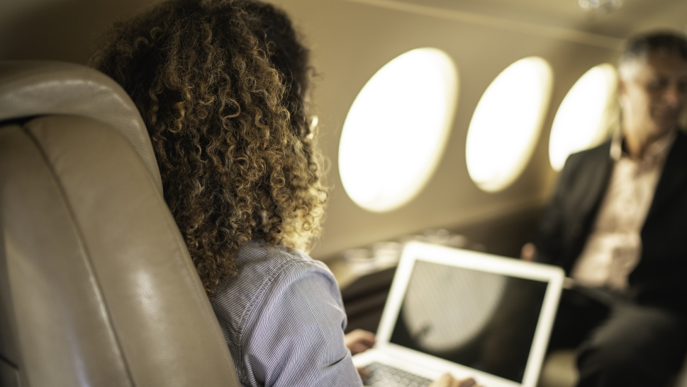Businesswoman looks at laptop in Beechcraft King Air cabin