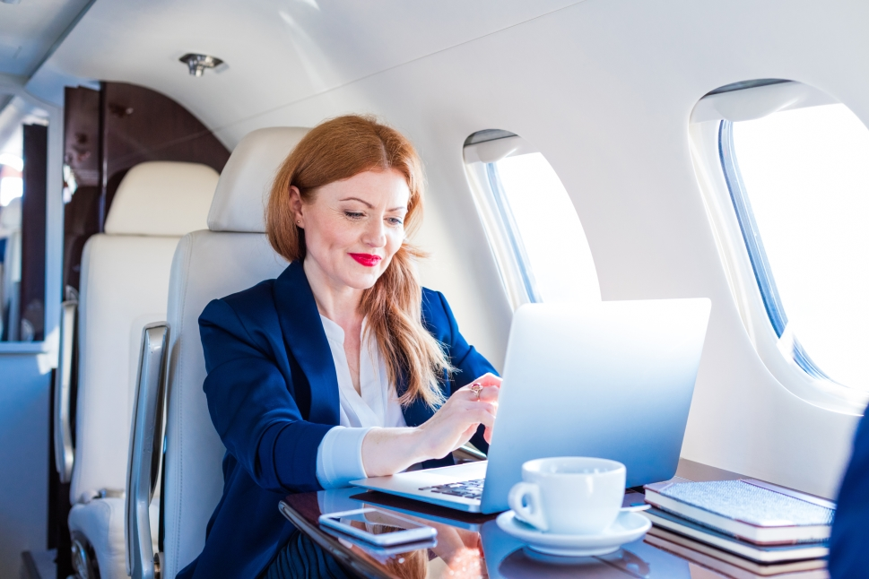 Successful businesswoman works on board a Mid-Size private jet