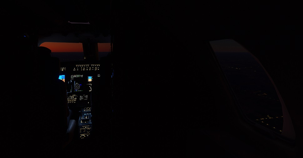 A private jet avionics panel glows in the cockpit during a night flight