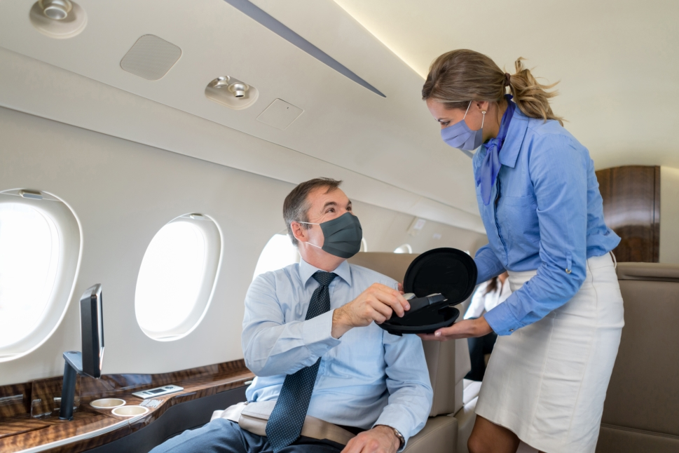 Private jet stewardess and executive passenger wearing face masks