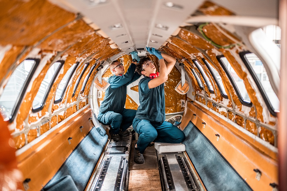 Airplane mechanics install electronics into a private jet cabin