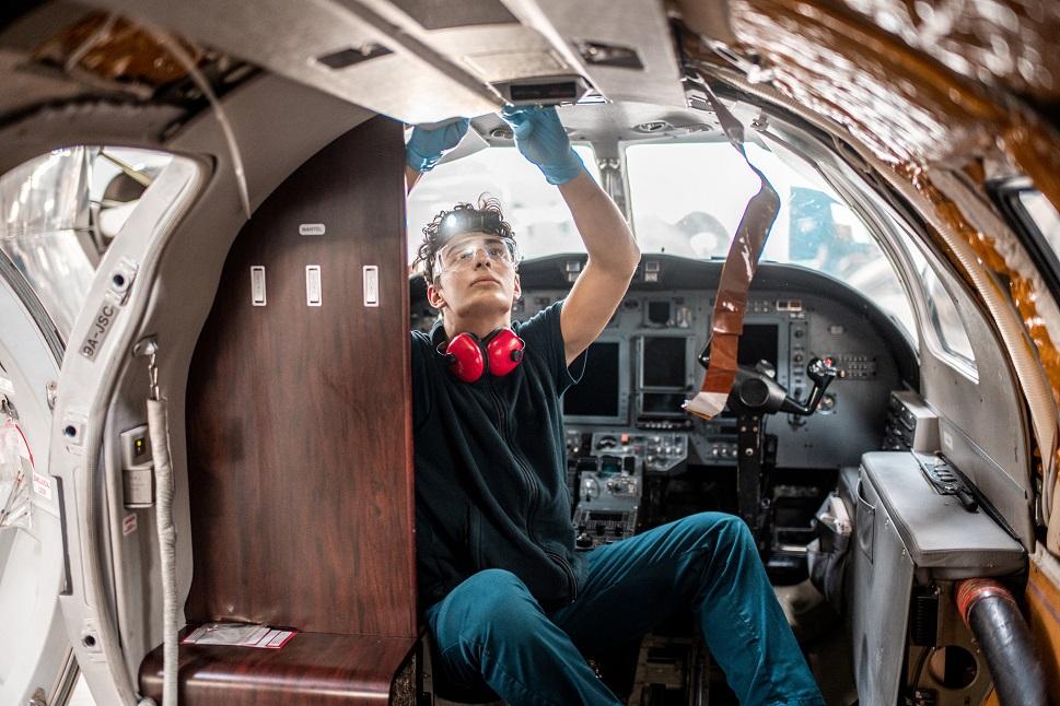 An avionics technician working on a light jet's wiring