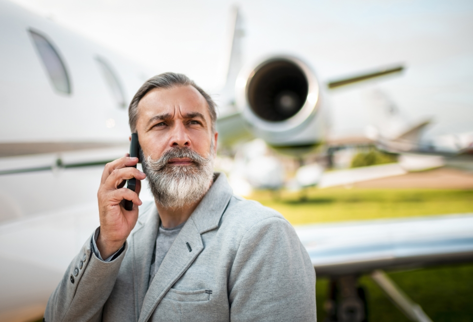 Private jet passenger boards airplane using his cell phone