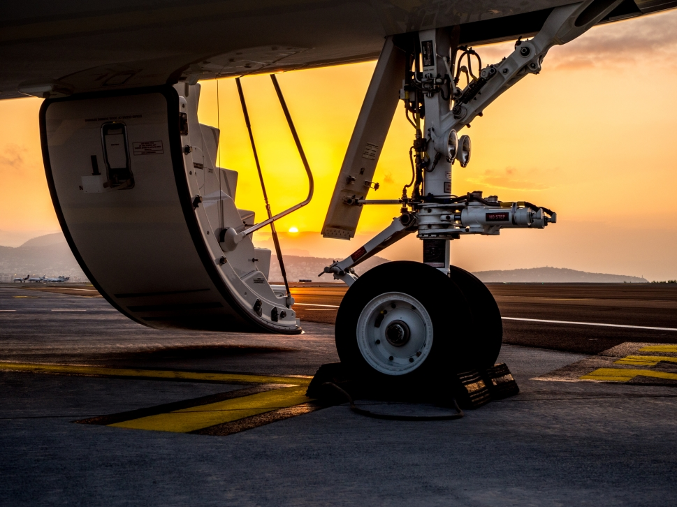 Private jet stairs and front wheel in front of sunset
