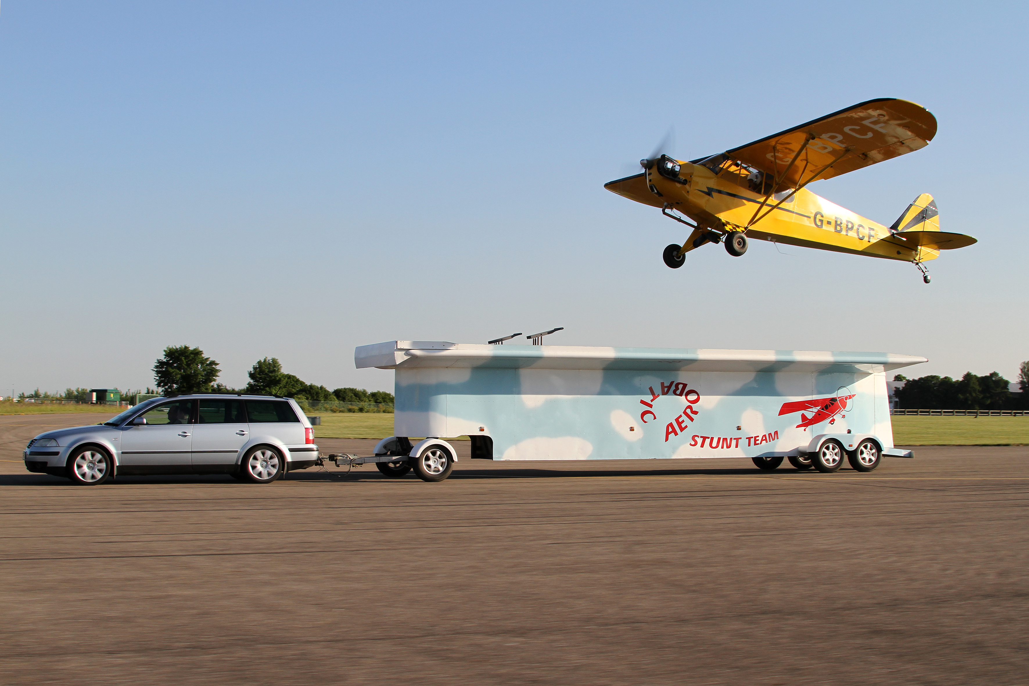 Single-engine piston aerobatics airplane flies over stunt team truck