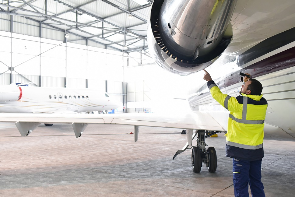 An aircraft mechanic examines a private jet's engine with a torch