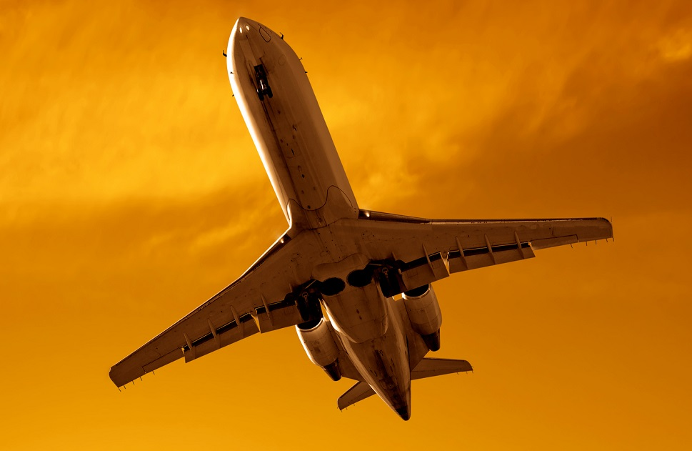 A private jet flies overhead in a sunset sky
