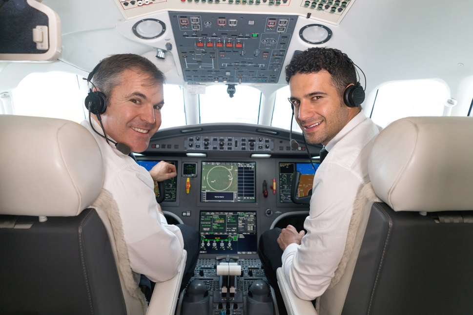 A pilot and co-pilot together in a private jet cockpit
