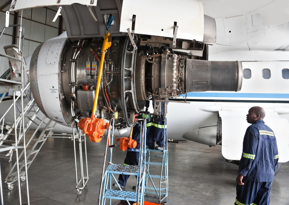 Aircraft mechanic inspects Bombardier private jet powerplant
