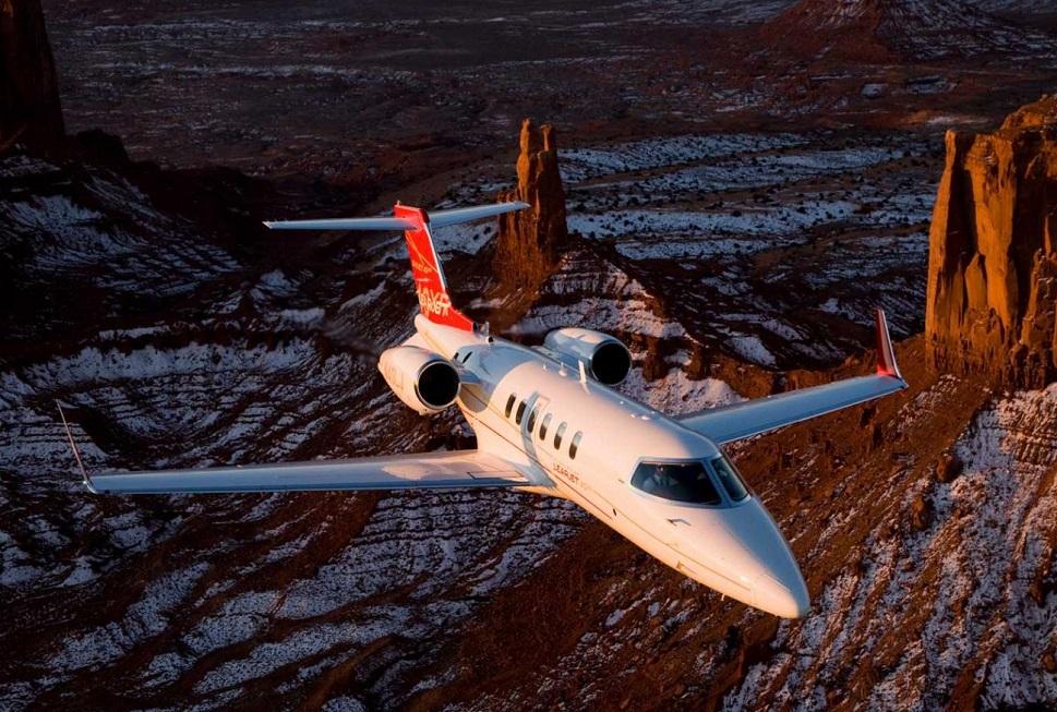 Bombardier Learjet 40XR Mid-Size jet flies over rocky terrain