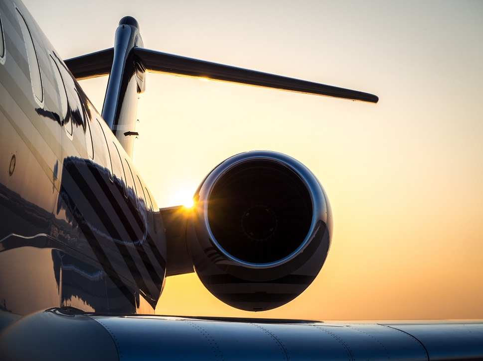Over-wing scene of a business jet lit up by sunrise