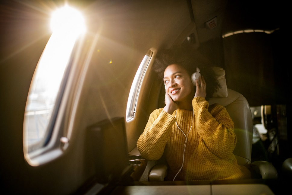 Young woman listens to music in a Cessna Citation jet cabin