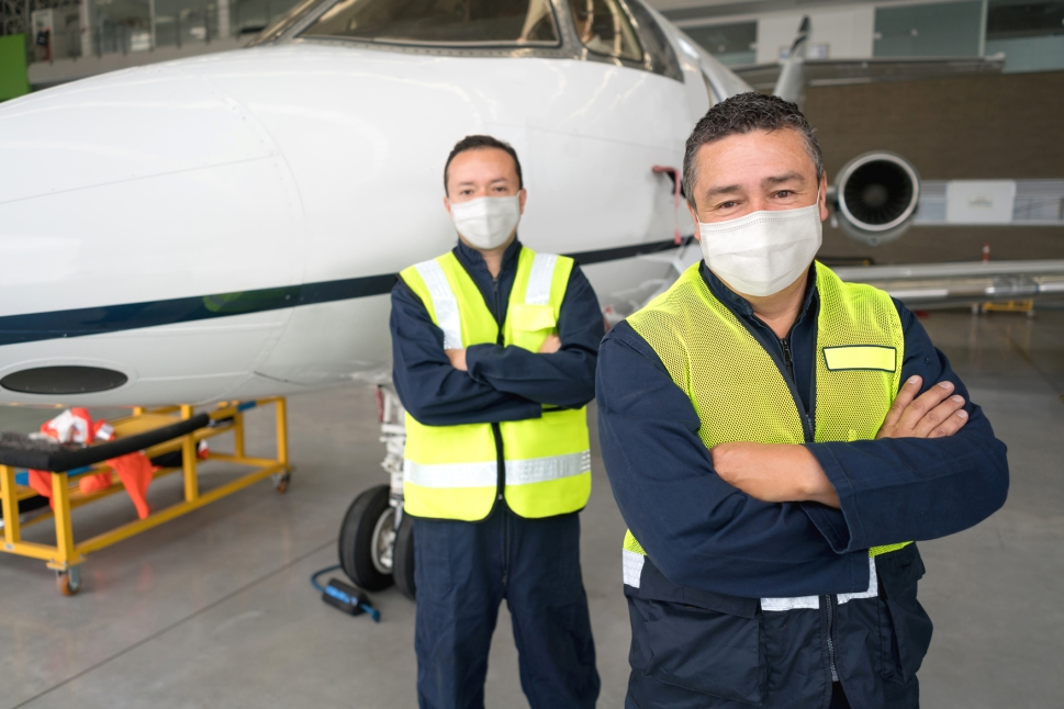 Private jet mechanics stand in front of business aircraft in hangar