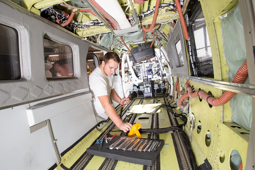 An airplane mechanic installs a new multi-mission interior to turboprop