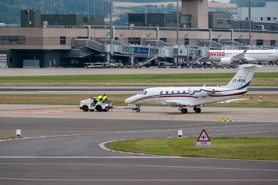 An aircraft tug tows a private jet along an airport taxiway