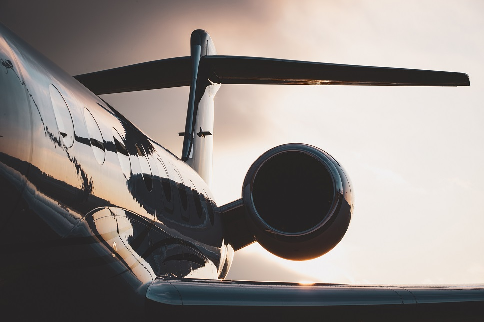 Over-wing photo of a Gulfstream private jet's tail and engine