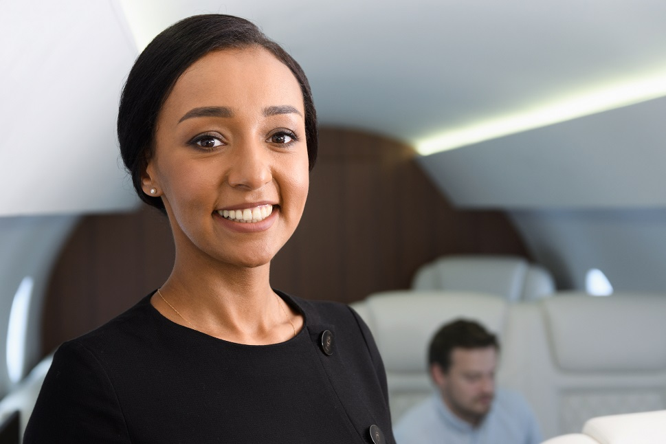 Private jet cabin attendant smiling