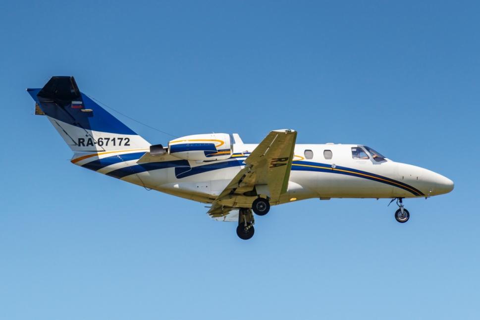 Cessna Citation CJ1 flying low in blue sky